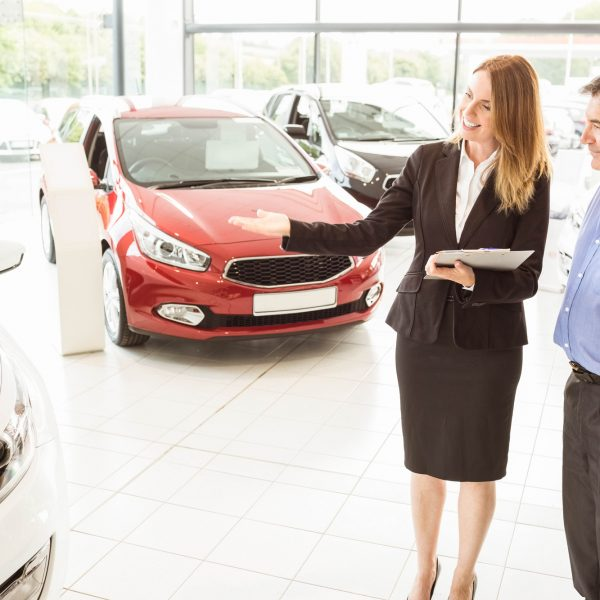 Smiling businesswoman showing car to customer at new car showrom